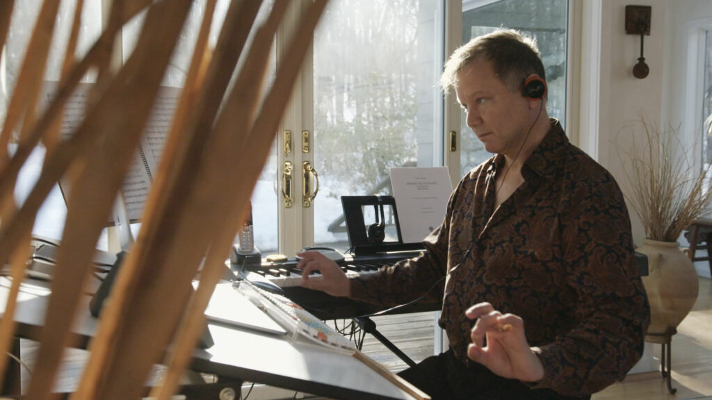 A man sits at a table composing music