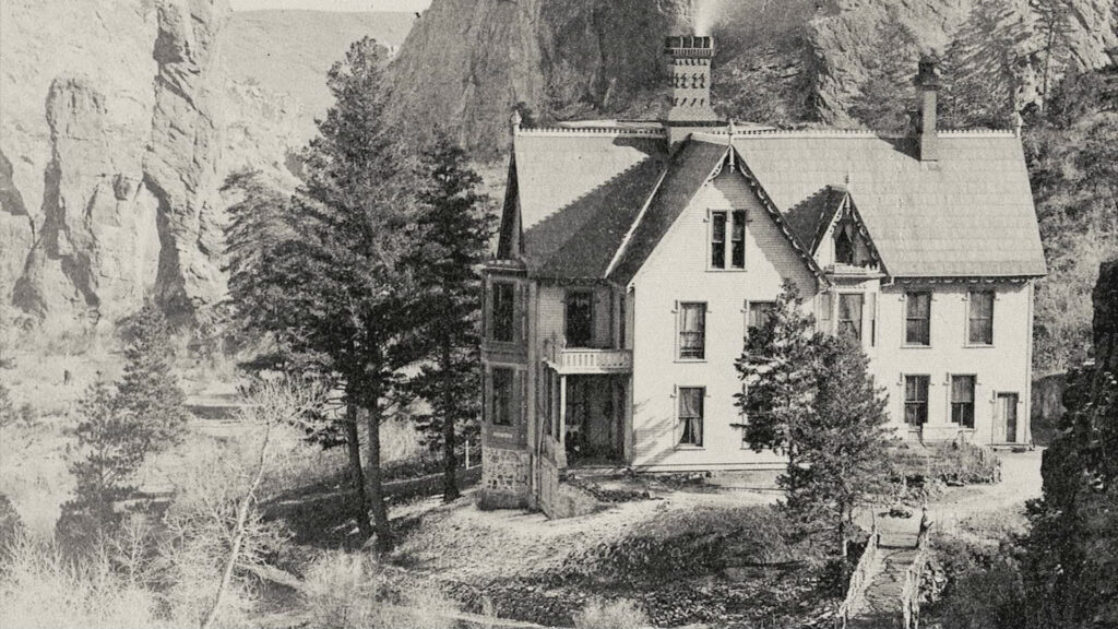 A black and white image of a whole in the mountains with trees