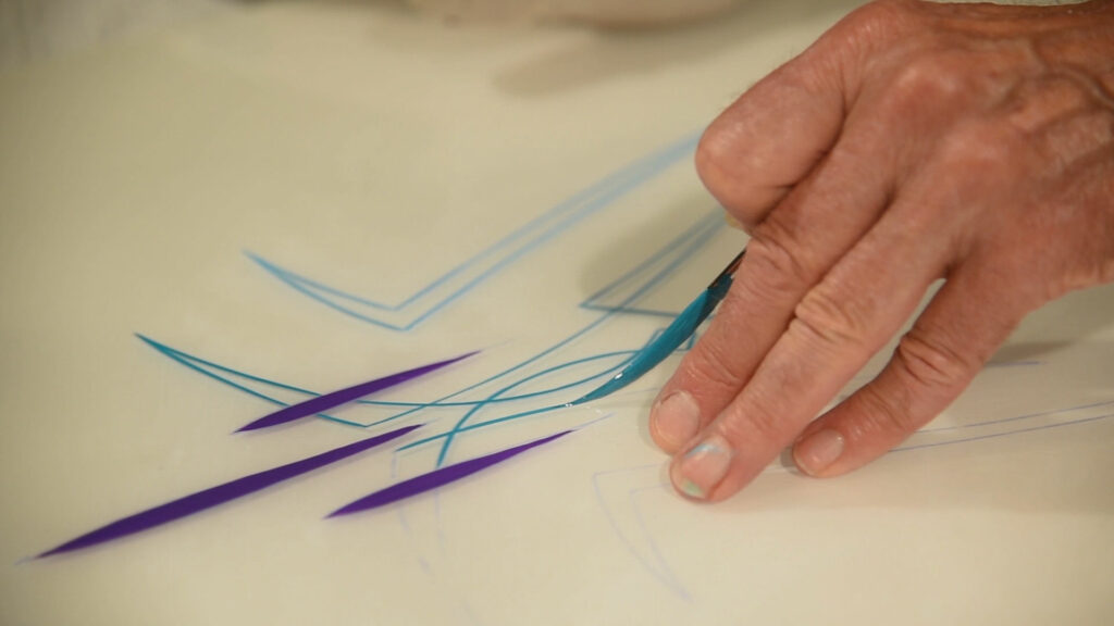"""A hand holding a paint brush carefully paints blue and purple lines called """"pinstriping"""""""