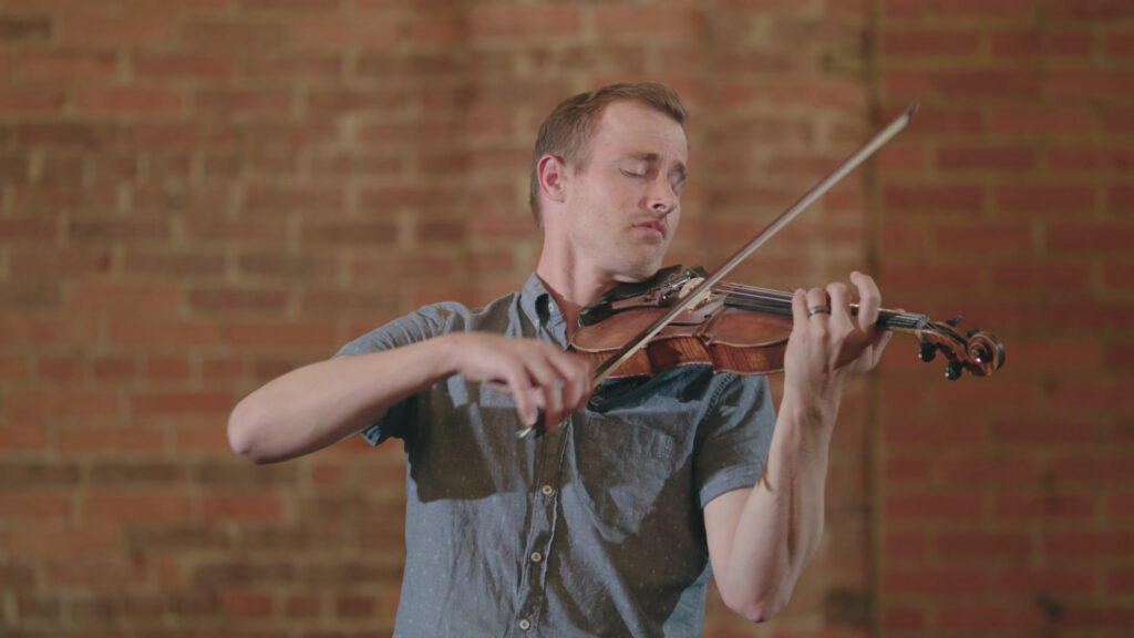 a man plays the violin in front of a brick background