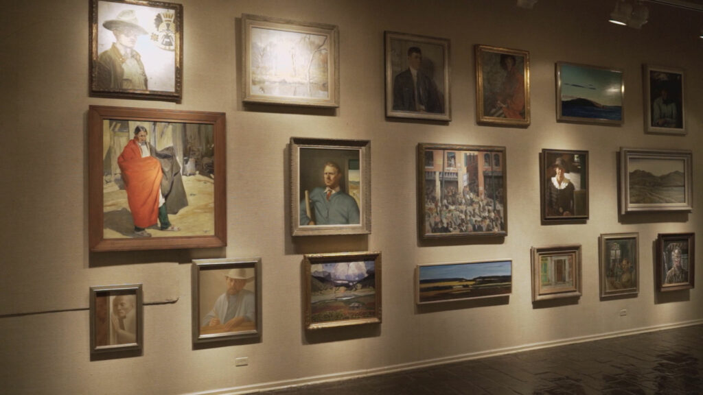 A gallery wall dimly lit with portraits hanging on it