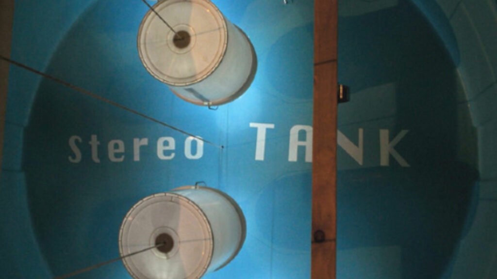 """A blue background with """"Stereo Tank"""" printed on it with two white circular tanks on it"""