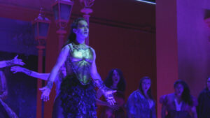 An actor in costume performing in blue lighting