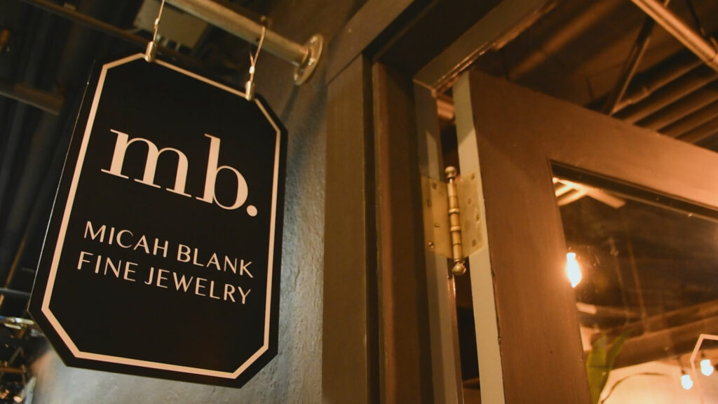 A hanging business sign for Micah Blank Fine Jewelry