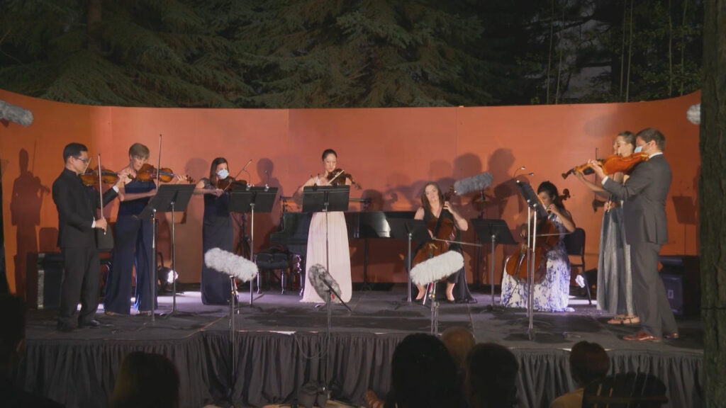 A group of musicians performing outside on a stage