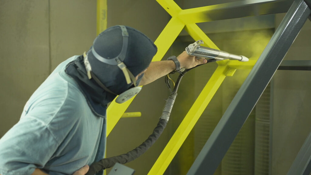 A person spraying paint onto a metal structure