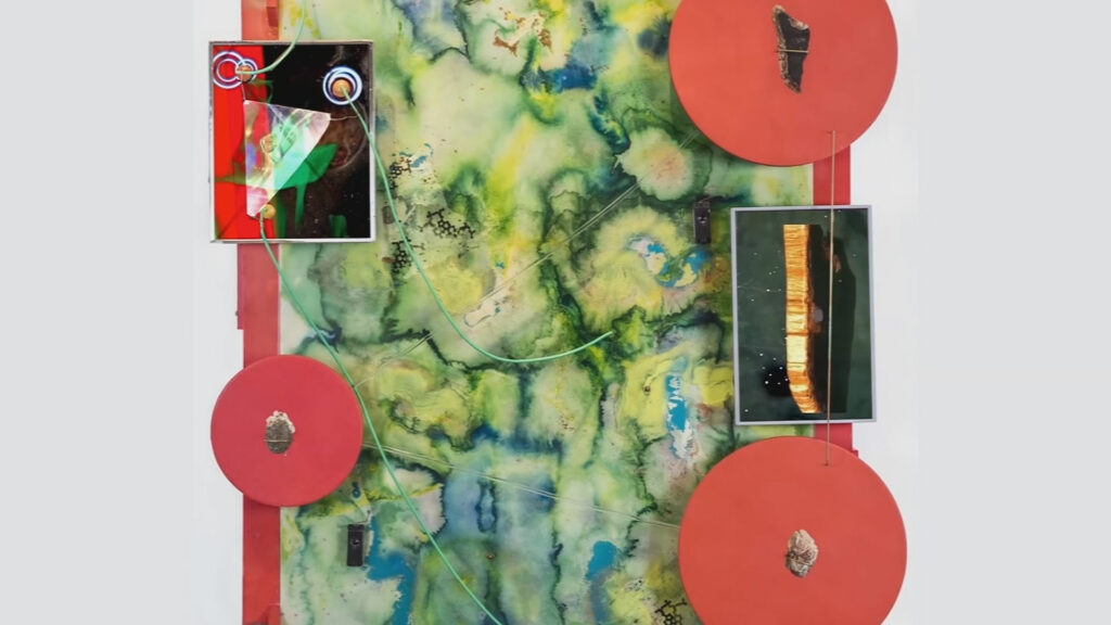 A colorful art piece of a green rectangle, red circles, and smaller images decorating it
