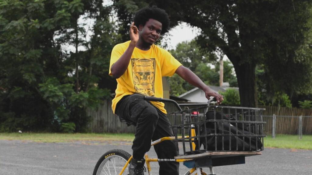 A person rides a bike waving at the camera