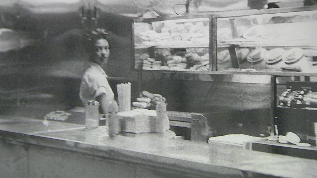A black and white photograph of a waitress at a diner