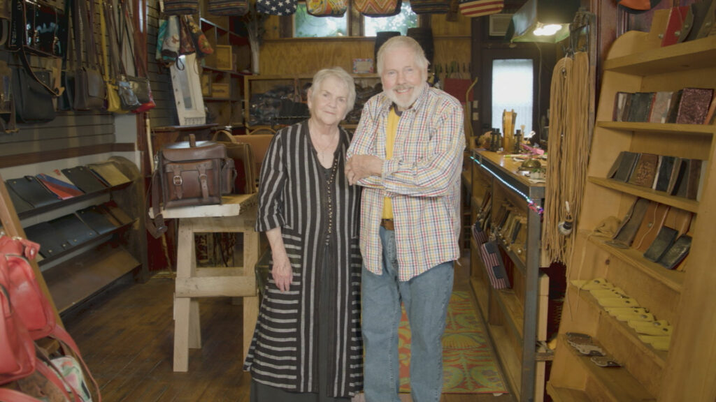 A couple stands together in a shop selling leather goods