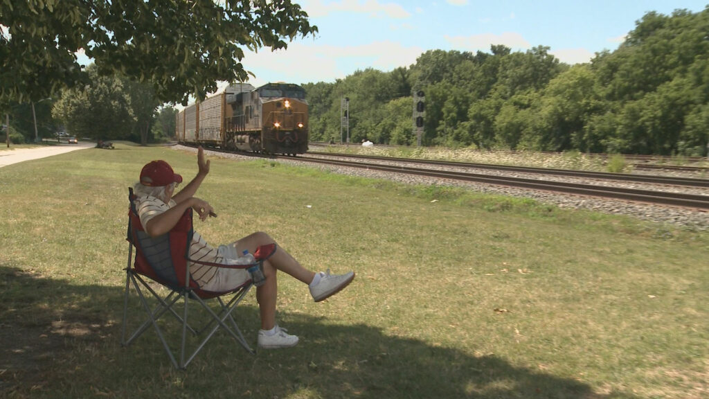 A person sitting in a chair waves at a passing by train
