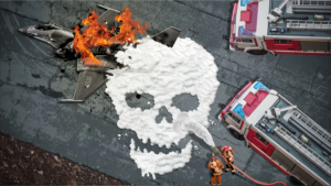 A graphic of firefighters extinguishing a crashed plane on fire with foam that is in the shape of a skull