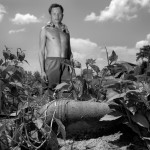 A farmer stands behind a live mortar he found in the field behind his home, near the Lan Som 719 battle site. A branch of the Ho Chi Minh Trail once ran through this valley, and the man says the surrounding hillsides are still covered in unexploded bombs, which makes him afraid whenever he goes out farming.