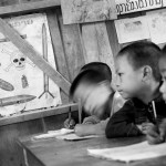 Children study beneath a UXO warning poster in the one-room schoolhouse in Ban Pakeo.