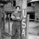 Sou Lin Phan poses next to a large dud bomb in the middle of his village in rural Xieng Khouang Province.