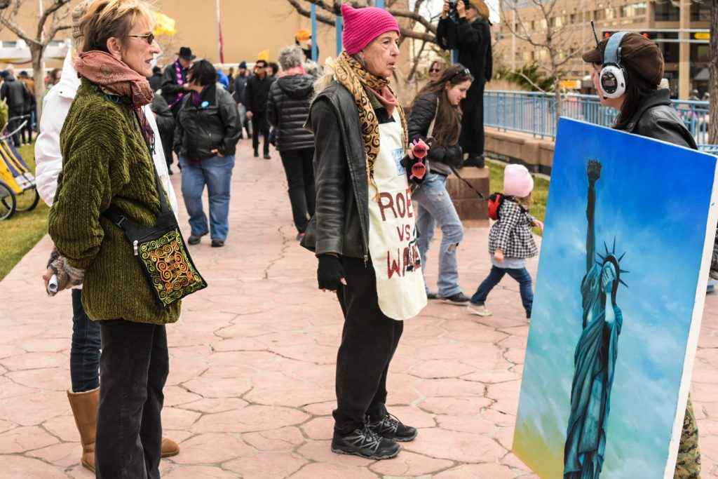 "Katie Neeley, far right, exhibits her Oil Painting ""My Lady,"" on Civic Plaza, Saturday, Jan. 21st, 2017, in Albuquerque, NM. The rally in Albuquerque was a single gathering held in concert with hundreds of rallies and marches spread across the country and around the world. The sister rally in Civic Plaza was ""to show solidarity across the nation and at home,"" according to social media accounts affiliated with the rally. (Kevin Maestas)"