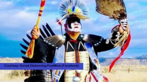 """An Indigenous dancer performs, with text """"Social Distancing PowWow""""."""