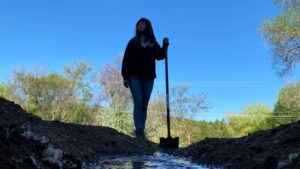 A person stands in dirt, holding a shovel in their hand.