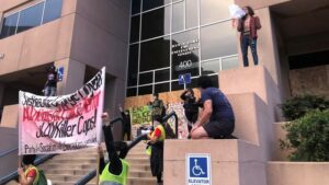 A group of demonstrators give speeches and hold signs in front of the Albuquerque Police Department during the day.