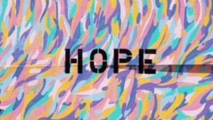 """A painting with text reading """"HOPE"""" in front of colorful wisps."""
