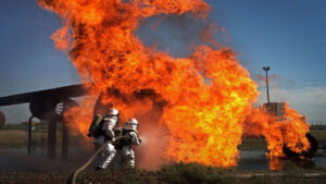 Firefighters in silver fire proximity suits hose down a giant flame.