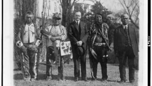 Native men and a white man stand next to each other for an antique photo.