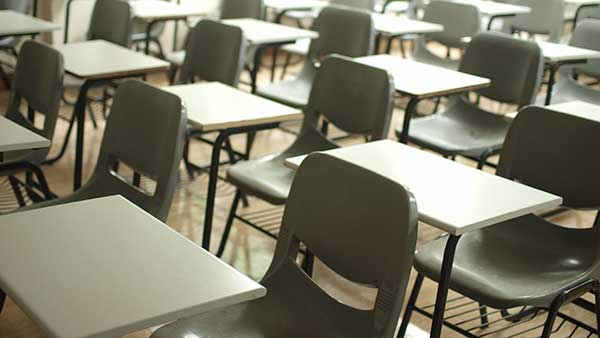 Close-up of chairs and desks in an empty classroom.
