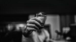 A hand holds up a crumpled $1 dollar bill.