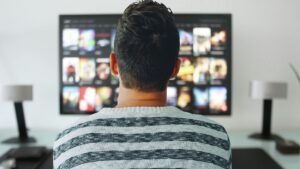 A person sits in front of a television screen, selecting from a gallery of titles.