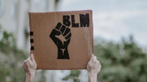 """Hands hold up a cardboard sign with a fist drawn on it and """"BLM""""."""