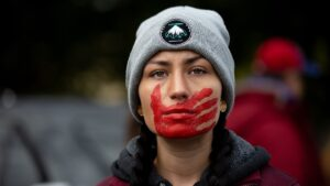 A demonstrator wearing a beanie depicting four feathers, and a red handprint covering their mouth.