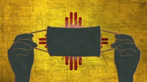 Composite illustration of hands holding a facemask covering a coronavirus on top of the New Mexican flag.
