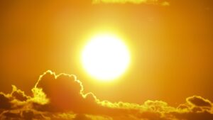 Close-up of the Sun blazing heat through a partly cloudy sky.