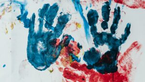 A canvas with assorted fingerpainted markings, including two handprints.