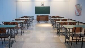 An empty classroom with desks and a chalk board on the wall.
