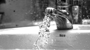 A black and white photo of a faucet gushing water into a sink.