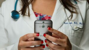 A closeup of a doctor holding a phone in their hands.