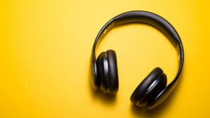 A pair of wireless headphones laying on a yellow backdrop.
