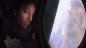 A woman looks out of a window down at Earth from a Virgin Galactic craft.
