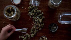 A mason jar of cannabis spilled on a table.