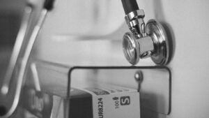 A black and white image of a stethoscope and other hospital items