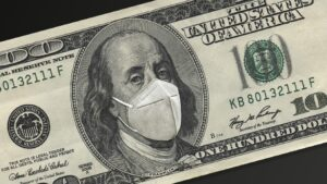 A $100 dollar bill, with a facemask covering Benjamin Franklin's face.