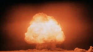 An atomic bomb explodes in a vast field.
