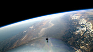 The wing of a Virgin Galatic ship looking over Earth.
