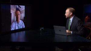 A man with a laptop speaks with someone over videochat on a television.