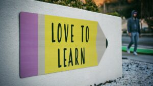 """A sign with a pencil with """"Love to Learn"""" printed inside."""