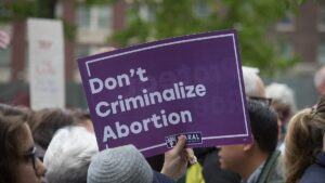 """A crowd of people and a sign being held up that say """"Don't Criminalize Abortion"""""""