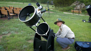 A scientist in outdoor clothing prepares a large telescope on grass.