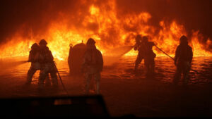 A group of firefighters spray water and combat a giant blaze in a body of water.