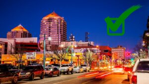 Downtown Albuquerque at Night with a green square and check mark graphic